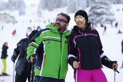 Glückliche Paare, die im Schnee genießen Lizenzfreie Stockfotos