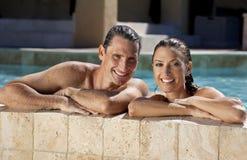 Glückliche Paare, die im Swimmingpool sich entspannen Stockfotos
