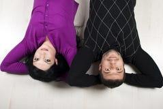 Glückliche Paare, die sich auf Fußboden hinlegen Stockfotografie