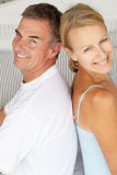 Glückliche Paare, die zurück zu Rückseite sitzen Lizenzfreies Stockfoto