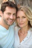 Glückliche Paare gestanden vor Baum Lizenzfreies Stockfoto