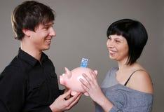 Glückliche Paare mit piggybank Stockfotos