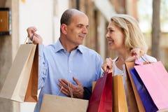 Glückliche reife Familie, die Taschen nach dem Einkauf hält Lizenzfreies Stockbild