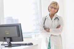 Glückliche reife Ärztin Standing Arms Crossed im Krankenhaus Lizenzfreies Stockfoto