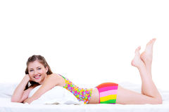 Glückliche schöne junge Frau, die im Bett liegt Stockfotos