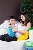 Glückliche schwangere Paare nähern sich dem Weihnachtsbaum Stockfotografie