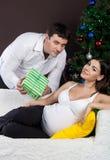 Glückliche schwangere Paare nähern sich dem Weihnachtsbaum Stockfoto