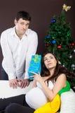 Glückliche schwangere Paare nähern sich dem Weihnachtsbaum Stockfotos