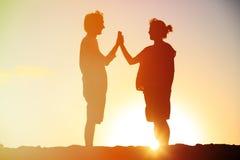 Glückliche schwangere Paare am Sonnenuntergangstrand Stockbild