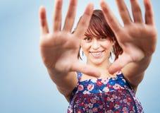 Glückliche spielerische jugendlich Frau, die durch Hände schaut Lizenzfreie Stockfotos