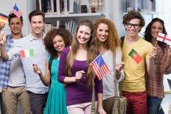 Glückliche Studenten, die internationale Flaggen wellenartig bewegen Stockfoto