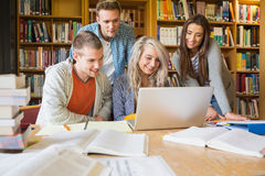 Glückliche Studenten, die Laptop am Schreibtisch in der Bibliothek verwenden Lizenzfreie Stockfotos