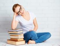 Glückliche Studentin, welche die Hausarbeit, bereitend für die Prüfung wi vorbereitet vor Stockfoto