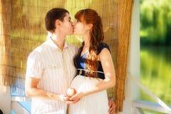 Glückliche und der Junge schwangere Paare, die im Park umarmen Sommer vaca Stockfoto