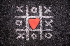Glückliche Valentinsgrußtageskarte, Tic tac-Zehenspiel aus den Grund, xoxo und Stein Stockfoto
