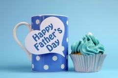 Glückliche Vatertagsmitteilung auf blauer Thematupfen-Kaffeetasse mit kleinem Kuchen. Stockfotografie