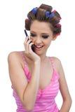 Glückliche vorbildliche tragende Haarrollen, die einen Anruf haben Lizenzfreies Stockbild