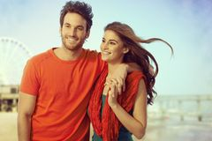 Glückliche zufällige Paare, die am Meerblickstrand gehen Lizenzfreie Stockfotografie
