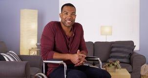 Glücklicher afrikanischer Mann, der beim Rollstuhllächeln sitzt Lizenzfreies Stockfoto