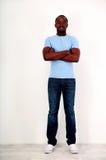 Glücklicher afrikanischer Mann, der mit den Armen gefaltet steht Stockfotografie