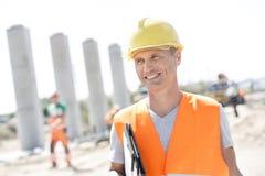 Glücklicher Architekt, der beim Halten des Klemmbrettes Baustelle weg betrachtet Lizenzfreie Stockfotos