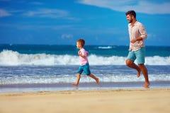 Glücklicher aufgeregte Vater und der Sohn, die auf Sommer läuft, setzen auf den Strand, genießen das Leben Lizenzfreie Stockfotos