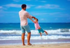 Glücklicher aufgeregte Vater und der Sohn, die auf Sommer spielt, setzen auf den Strand, genießen das Leben Stockbild