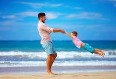 Glücklicher aufgeregte Vater und der Sohn, die auf Sommer spielt, setzen auf den Strand, genießen das Leben Lizenzfreies Stockbild