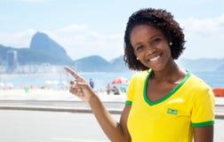 Glücklicher brasilianischer Sportfan, der auf Sugarloaf-Berg zeigt Stockfotografie