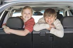 Glücklicher Bruder And Sister Leaning auf Auto Seat Stockbild
