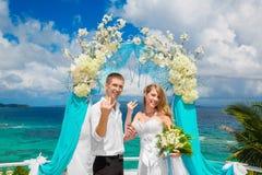 Glücklicher Bräutigam und Braut mit Eheringen unter dem Bogen verzieren Stockbilder