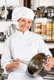Glücklicher Chef-Mixing Egg With-Draht wischen Stockfoto