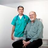 Glücklicher Doktor mit glücklichem älterem männlichem Patienten Stockbild