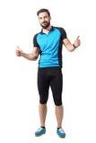 Glücklicher erfolgreicher Sportradfahrer im blauen Trikot, das Daumen zeigt, up Handzeichen Lizenzfreies Stockbild