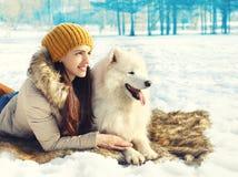 Glücklicher Fraueneigentümer mit dem weißen Samoyedhund, der zusammen auf Schnee liegt Lizenzfreie Stockfotos