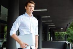 Glücklicher hübscher junger Geschäftsmann, der Laptop steht und hält Stockfoto