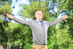Glücklicher Herr, der seine Arme in einem Park verbreitet Stockbilder