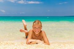 Glücklicher jugendlich Junge, der auf dem Strand sich entspannt Tropisches Meer im backgr Stockfoto