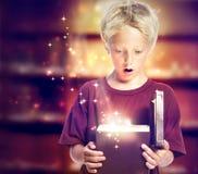 Glücklicher Junge, der einen Geschenk-Kasten öffnet Stockfotos