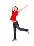 Glücklicher Junge, der mit den angehobenen Händen oben springt Stockfotos