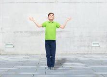 Glücklicher Junge im Polot-shirt, das oben Hände anhebt Lizenzfreie Stockfotografie