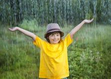 Glücklicher Junge im Regensommer Stockfoto