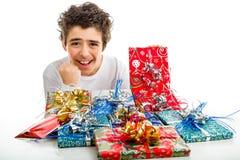 Glücklicher Junge macht das Erfolgszeichen, das Weihnachtsgeschenke empfängt Stockfotos