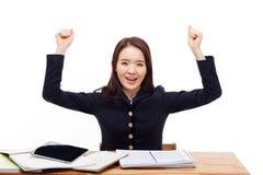 Glücklicher junger asiatischer Student auf dem Schreibtisch Lizenzfreie Stockbilder