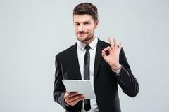 Glücklicher junger Geschäftsmann mit Tablette okayzeichen blinzelnd und zeigend Stockbild