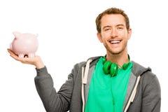 Glücklicher junger Mann, der Geld in das Sparschwein lokalisiert auf Weiß einsetzt Lizenzfreies Stockbild