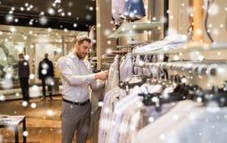 Glücklicher junger Mann, der Kleidung im Bekleidungsgeschäft wählt Lizenzfreies Stockfoto
