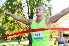 Glücklicher junger männlicher Läufer, der auf Rennende gewinnt Stockfoto