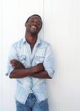 Glücklicher junger schwarzer Mann, der draußen gegen weißen Hintergrund lächelt Stockfotografie
