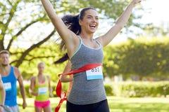 Glücklicher junger weiblicher Läufer, der auf Rennende gewinnt Stockfoto